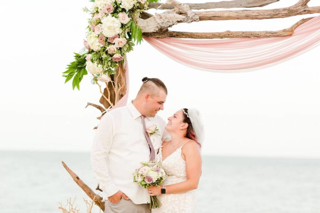 Outer Banks Vow Renewal Couple looking at each other smiling in front of wedding arch
