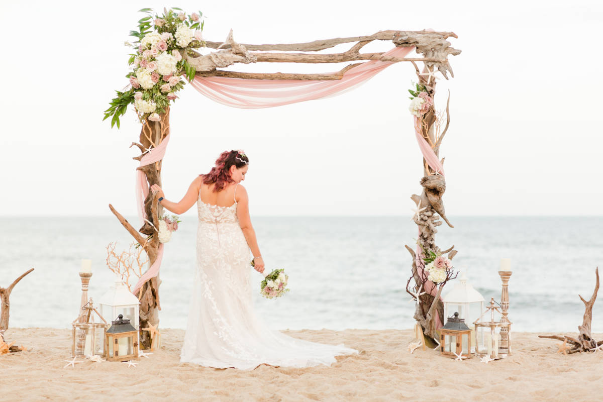 Outer Banks Wedding Arch ceremony set up with Bride leaning against arch and holding bouquet