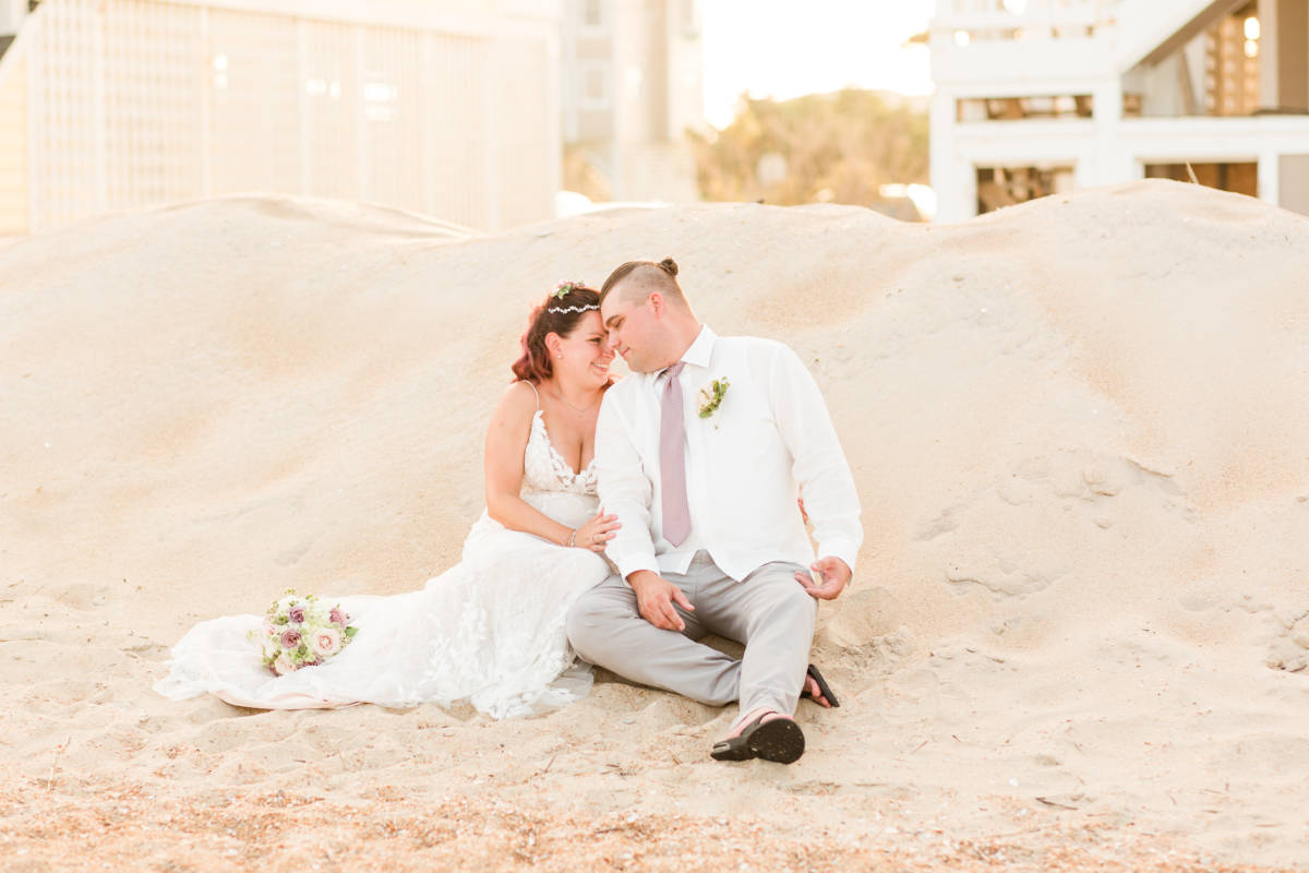 Outer Banks Vow Renewal Couple sitting on beach looking into each other's eyes