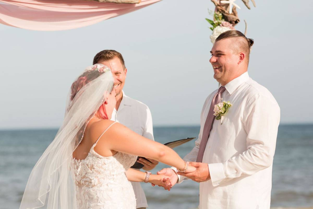 Outer Banks Wedding Ceremony with Officiant and Couple holding hands smiling